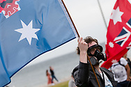 A man wearing a gas mask is seen holding  a flag during the Sack Daniel Andrews Protest in St Kilda. Parts of the community are looking to hold the Victorian Premier accountable for the failings of his government that led to more than 800 deaths during the Coronavirus crisis. Victoria has recorded 36 days Covid free as pressure mounts on the Premier Daniel Andrews to relax all remaining restrictions. (Photo by Dave Hewison/Speed Media)