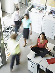 Oct. 07, 2006 - Young woman in a yoga position sitting on her work desk. Model and Property Released (MR&PR) (Credit Image: © Cultura/ZUMAPRESS.com)