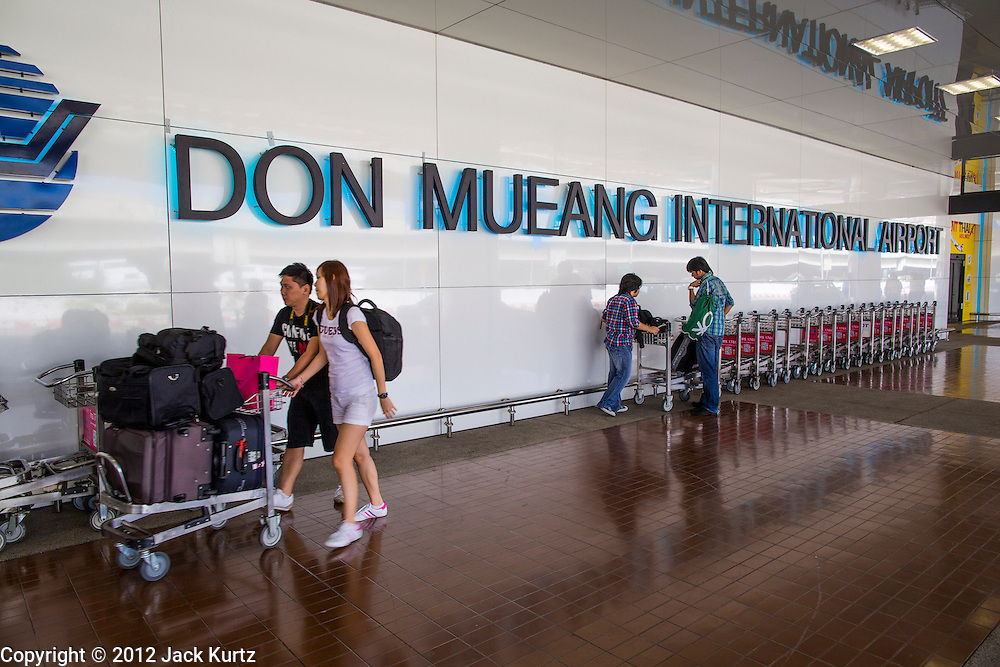 01 OCTOBER 2012 - BANGKOK, THAILAND: Passengers get luggage carts before walking in Don Mueang International Airport in Bangkok during the airport's reopening. Don Mueang International Airport is the smaller of two international airports serving Bangkok, Thailand. Don Mueang was officially opened as a Royal Thai Air Force base on 27 March 1914 and commercial flights began in 1924. Don Mueang Airport closed in 2006 following the opening of Bangkok's new Suvarnabhumi Airport, and reopened as a domestic terminal for low cost airlines after renovation on 24 March 2007. Closed during the flooding in 2011, Don Mueang was again renovated and reopened in 2012 as the airport for low cost airlines serving both domestic and international passengers. On Monday, Air Asia, Asia's leading low cost airline, transferred all of their flight operations to Don Mueang and the airport was officially reopened. Suvarnabhumi International Airport is already over capacity and Don Mueang's importance as a hub is expected to grow.    PHOTO BY JACK KURTZ
