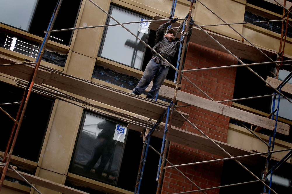 A construction worker assembles scaffolding on the exterior of a new, up-scale apartment building being built on a former vacant lot in the northeast section of Spanish Harlem, Summer 2005. A sign of the gentrification of the neighborhood.