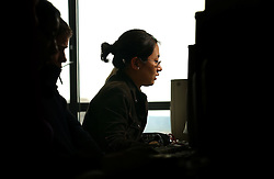 PARIS -  FRANCE - APRIL-21-2004 - Male and female students work in a university computer lab. <br /> <br /> technology - business - computer - wifi - wireless - internet - communication - email - www - world wide web - web surfing - connect - connecting - connected - connectivity - study - studying - research - academics - education - student - university - young - adult - male - man - woman - female - asian - think - thinking - concentrate - concentration - concentrating - silhouette - model released