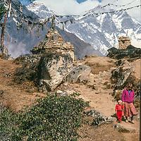 Meredith Wiltsie & 3-year old son Ben trek past a Tibetan Buddhist chorten while trekking  in the Khumbu Region of Nepal, with Mount s Everest &  Lhotse  in background.