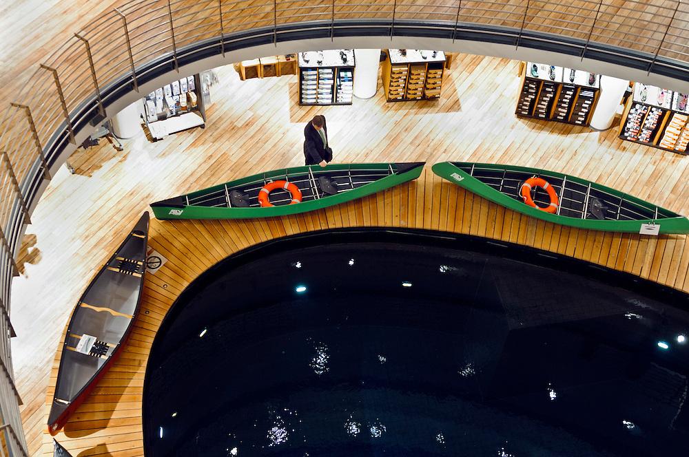 Deutschland, NRW,Nordrhein-Westfalen, Köln, Ein Mann in einem Anzug schaut sich in einem Outdoor-Geschäft ein Kanu an |  Germany,Cologne,A man in an outdoor store  is looking at a canoe