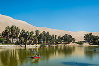people run boats at Huacachina lagoon in the peruvian coast at Ica Peru