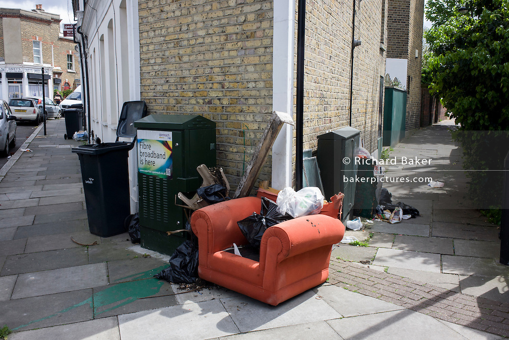 Dumped armchair and other domestic rubbish, fly-tipped on a street corner in south London.