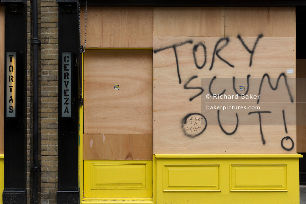 """During the UK's Coronavirus pandemic lockdown and on the day when a further 255 deaths occurred, bringing the official covid deaths to 37,048, <br /> and seen the day after the very unusual press conference by UK Prime Minister's special advisor Dominic Cummings about his breaking of lockdown rules, the message """"Tory Scum Out!"""" has been written on plyboard on a closed business in Soho, on 26th May 2020, in London, England."""