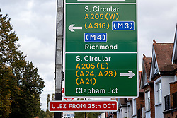 Licensed to London News Pictures. 24/10/2021. London, UK. A ULEZ sign at traffic lights crossing the South Circular at Putney today. Tomorrow the London Ultra-Low Emission Zone (ULEZ) area will expand to inside the North and South Circular with many drivers of older cars forced to pay a daily £12.50 fee or face heavy fines of £160.00. Photo credit: Alex Lentati/LNP