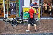 Nederland, Nijmegen, 9-8-2019Een medewerker van pakketbedrijf DHL levert bestellingen af in een winkelstraat. Hij heeft een speciale fiets , vrachtfiets met aanhanger die het bezorgen in de bnnenstad, stadscentrum, voetgangersgebied, autovrije straat, makkelijker maakt .Foto: Flip Franssen