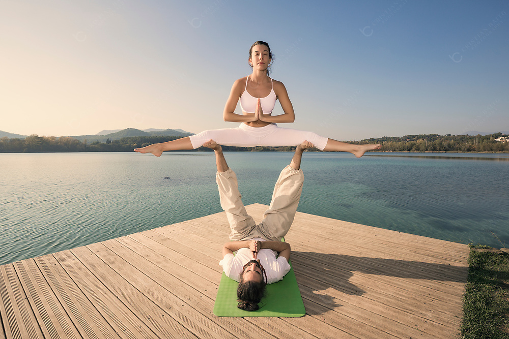 Couple practicing acroyoga in nature at beautiful lake Couple doing acroyoga in nature