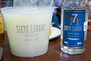 Siete Leguas blanco tequila and margarita mix on the bar for self service at the Fellos Bar in Atotonilco de Alto, Jalisco, Mexico. The bar has been a meeting place for tequila distillery owners and workers for more than 50-years in the tiny mountain town of Atotonilco de Alto, home to Siete Leguas, Don Julio and Patron tequila brands.