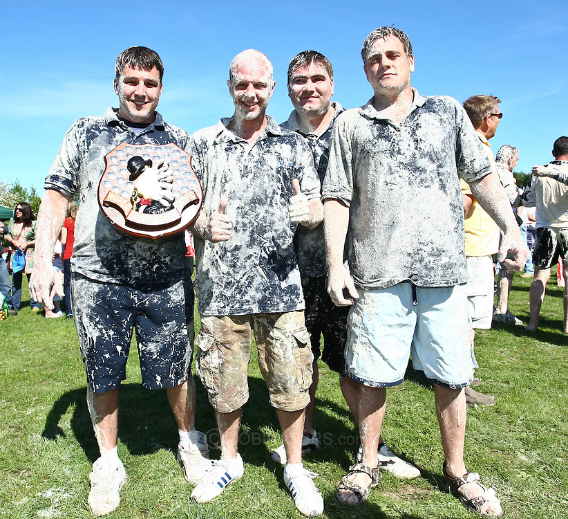 Coxheath, Kent - Saturday, May 22nd 2010: New world custard pie champions The High Pressure Cleaning Company hold their trophy after beating Coxheath 96-56 in the finals at the World Custard Pie Championships at Coxheath near Maidstone, Kent. Left to right: Karl Hickmott (Stockbury), Terry Hadaway (Maidstone), Glen Draper (Maidstone), Jimmy Hickmott (Stockbury). The first championship was held in 1967 in Coxheath using a special custard recipe developed by Richard Hearn aka Mr Pastry. The championship is made up of teams competing in heats, semi finals and the final, with the number of pies available per team increasing from 5 in the heats to 10 in the final. 6 points are scored for a direct hit on the face, 3 points for the shoulders or upwards, 1 point for any other part of the body, and points are deducted for misses. A discretionary 5 points can be awarded for the most amusing and original throwing technique. The event is part of the Rotary Club funday. (Pic by Andrew Tobin/SLIK Images)