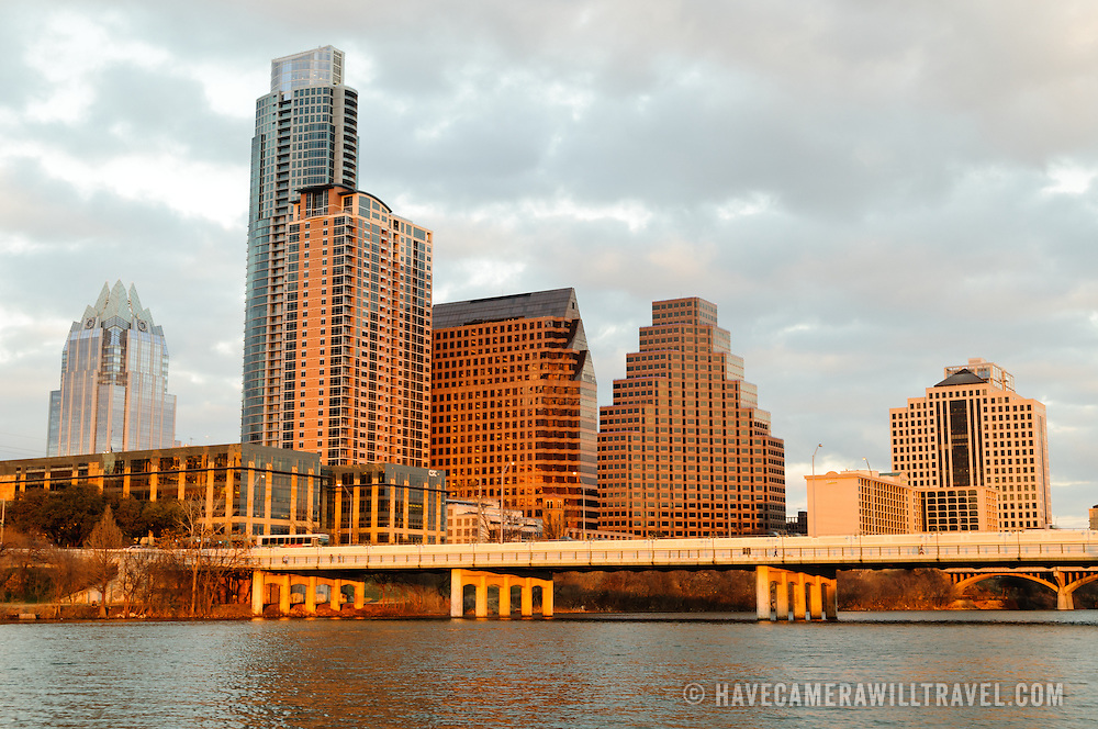 The city skyline of downtown Austin, Texas, as seen from across Town Lake, with the golden glow of the setting sun shining on the buildings.
