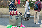 Asian woman wearing a hand knitten American flag style coat