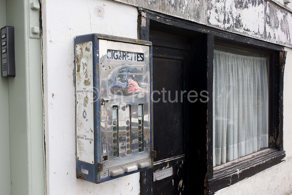 Old cigarette dispenser in a high street, Deal Kent. As a piece of bygone street fixture to a wall in this small town in south-eastern England, we see what used to be a common sight on Britain's streets, shops and pubs. Then, cigarette smoking was a national habit and before the changes of smoking in public laws by progressive governments who also banned the selling of tobacco anywhere, except in licensed premises. Yet somehow this old dispenser remains in place, a symbol of the way things were.
