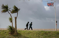 © Licensed to London News Pictures. 30/07/2021. Worthing, UK. Walkers struggle in high winds on the seafront at Worthing in West Sussex. Parts of the south are feeling the effects of Storm Evert, the first named storm of summer 2021. Photo credit: Peter Macdiarmid/LNP