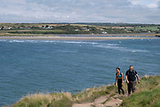 View of walkers along the coastal path on 17th August 2021 in Newport, Pembrokeshire, Wales, United Kingdom. Newport is a town, parish, community, electoral ward and ancient port of Parrog, on the Pembrokeshire coast in West Wales at the mouth of the River Nevern in the Pembrokeshire Coast National Park.