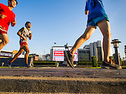 """11 DECEMBER 2014 - THONBURI, BANGKOK, THAILAND:  Boxers from the Kanisorn gym run laps at Wong Wian Yai traffic circle in Bangkok. The Kanisorn boxing gym is a small gym along the Wong Wian Yai - Samut Sakhon train tracks. Young people from the nearby communities come to the gym to learn Thai boxing. Muay Thai (Muai Thai) is a Thai fighting sport that uses stand-up striking along with various clinching techniques. It is sometimes known as """"the art of eight limbs"""" because it is characterized by the combined use of fists, elbows, knees, shins, being associated with a good physical preparation that makes a full-contact fighter very efficient. Muay Thai became widespread internationally in the twentieth century, when practitioners defeated notable practitioners of other martial arts. A professional league is governed by the World Muay Thai Council. Muay Thai is frequently seen as a way out of poverty for young Thais and Muay Thai camps and schools are frequently crowded. Muay Thai professionals and champions are often celebrities in Thailand.    PHOTO BY JACK KURTZ"""