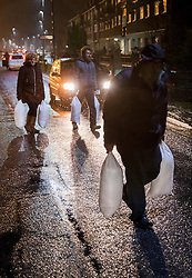 © Licensed to London News Pictures. 13/01/2017. Great Yarmouth, UK. Residents carry sandbags to their houses under threat of flooding in Great Yarmouth. The Environment Agency has warned residents to prepare for evacuation as as they fear flooding at tonight's high tide. Photo credit: Peter Macdiarmid/LNP