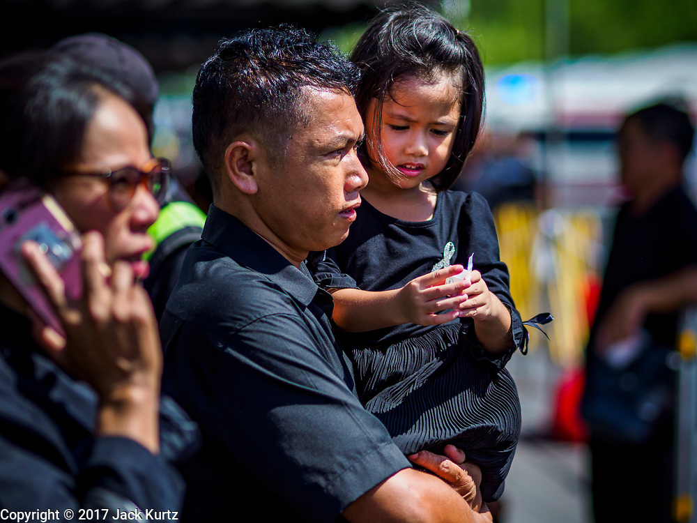 27 SEPTEMBER 2017 - BANGKOK, THAILAND: A man carries his daughter to the Grand Palace on their way to pay final respects to the funeral urn of the Late King. The Royal Household has announced that the palace will close to the public, including tourists, on 04 October 2017 to allow officials to complete preparations for the cremation of Bhumibol Adulyadej, the King of Thailand, who died on 13 October 2016. They also extended the official mourning period by 15 days. It was originally set to end on 13 October 2017 but now will end on 26 October 2017, the day of the King's cremation.    PHOTO BY JACK KURTZ