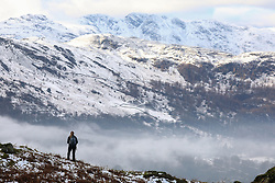 © Licensed to London News Pictures. 20/01/2019. Lake District, UK. A woman enjoys the view from the summit of Loughrigg Fell in the Lake District as the surrounding mountains are covered in snow and fog fills the valleys during cold weather. Photo credit : Tom Nicholson/LNP