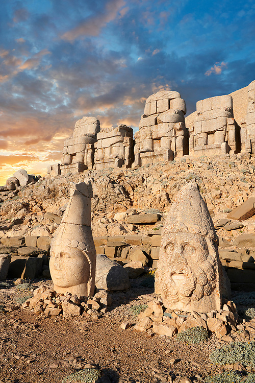 Statue heads at sunset, from right, Herekles & Apollo with headless seated statues in front of the stone pyramid 62 BC Royal Tomb of King Antiochus I Theos of Commagene, east Terrace, Mount Nemrut or Nemrud Dagi summit, near Adıyaman, Turkey .<br /> <br /> If you prefer to buy from our ALAMY PHOTO LIBRARY  Collection visit : https://www.alamy.com/portfolio/paul-williams-funkystock/nemrutdagiancientstatues-turkey.html<br /> <br /> Visit our CLASSICAL WORLD HISTORIC SITES PHOTO COLLECTIONS for more photos to download or buy as wall art prints https://funkystock.photoshelter.com/gallery-collection/Classical-Era-Historic-Sites-Archaeological-Sites-Pictures-Images/C0000g4bSGiDL9rw