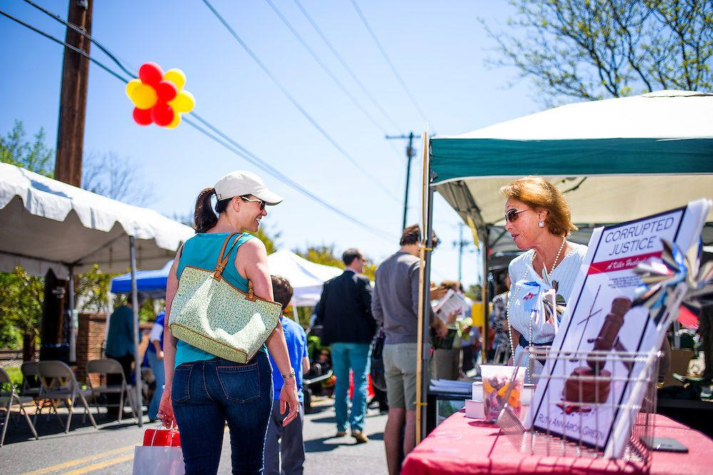 """Kensington, Maryland - April 24, 2016: Ruthann Aron Green offers candy to Connor Buss, 8, and his mother Kathi Buss, from Kensington. They're looking for a child's mystery book for Connor's book report due in one week. <br /> <br /> Ruthann Aron Green's autobiography """"Corrupted Justice -- A Killer Husband,"""" is centered around the circumstances leading up to her being convicted of trying to pay for her husband's murder in 1996.<br /> <br /> Former U.S. Senate candidate, lawyer and developer Ruthann Aron Green attempts to sell her autobiography """"Corrupted Justice -- A Killer Husband,"""" at the Kensington Book Festival in Kensington, Md., Sunday April 24, 2016. <br /> <br /> In 1997 Aron Green was recorded by an undercover police officer, posing as a hit-man, soliciting the murder of her husband, a wealthy urologist, and another man. After a high-profile arrest, a mistrial, and a second court cases ending in a no-contest plea, she was jailed from 1997 to 2000 at the Montgomery County Detention Center. She blames her mental state on an abusive relationship with Barry Aron, her husband. """"I had a psychotic break resulting from 30 years of abuse and over drugging of prescription drugs by my husband."""" <br /> <br /> After years away from Montgomery County, she's returned with a self-published autobiography as part of her campaign to re open her case and attempt to clear her name. If the case doesn't go her way, she opens herself up to be convicted for attempted murder.<br /> <br /> CREDIT: Matt Roth"""