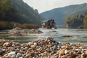 A floating Vietnamese mechanical gold dredge leaves a wake of tailing piles in the Nam Ou River, Laos.