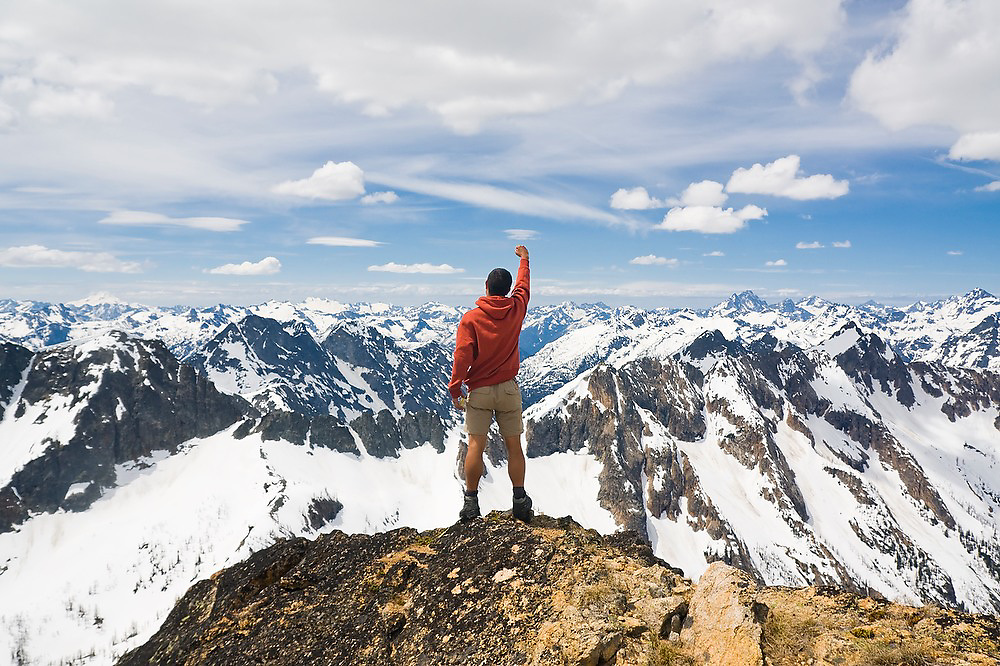 Climber Paolo Denti throws an arm into the air in celebration as he stands on the summit of Wallaby Peak, Okanogan National Forest, Washington, looking out into the Cascade Range.