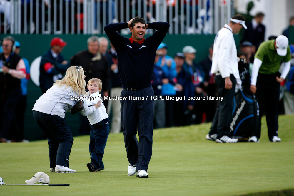 Padraig HARRINGTON (IRE) looks in disbelief that he has won,at 18th green with his wife Caroline picking their son Patrick during the play off at the British Open Championship, 22nd July 2007. At 18th with his family.