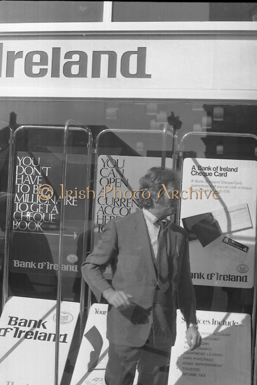 Fergus Rowan sits in at Bank of Ireland.  (J70)..1975..22.08.1975..08.22.1975..22nd August 1975..As a result of the 1970 bank strike which lasted for six months, the Rowan family business found itself in financial difficulties. During the strike the Rowans had had to accept cheques in good faith in order to stay in business. When the cheques came for settlement the bank refused as they stated that some were 'dodgy'. This put severe strain on the business which was eventually put into receivership.As part of the process the Rowan business beside the bank was put up for sale and was purchased by B.o I. Rowan was outraged and started a campaign against the bank which culminated in a sit in at the banks headquarters in Westmoreland St,Dublin. He also became a thorn in the side of the bank at the A.G.Ms raising many points...Picture of Fergus Rowan as he poses defiantly inside the bank's front window during his three day sit in.