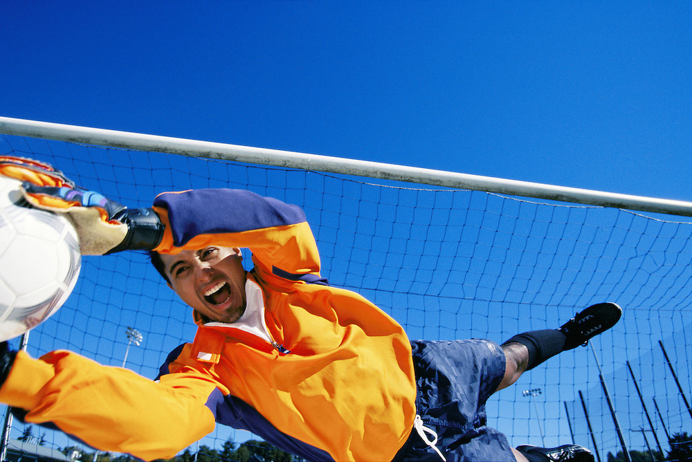 Soccer goalie diving to stop a shot on goal, low angle
