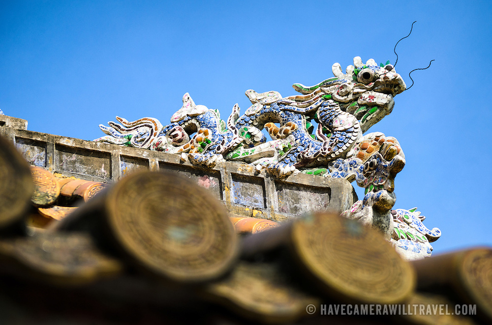 A sculpture of a dragon on a roof of a restored building at the Imperial City in Hue, Vietnam. A self-enclosed and fortified palace, the complex includes the Purple Forbidden City, which was the inner sanctum of the imperial household, as well as temples, courtyards, gardens, and other buildings. Much of the Imperial City was damaged or destroyed during the Vietnam War. It is now designated as a UNESCO World Heritage site.