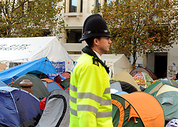 © Licensed to London News Pictures. 17/11/2011, London, UK. A policeman walks past Occupy London tents outside St Paul's Cathedral today 17 November 2011.  Photo credit : Stephen Simpson/LNP