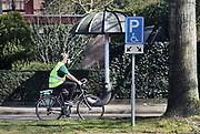Nederland, Wijchen, 5-4-2020  Een man rijdt op de fiets met een mondkapje, bril op en latex handschoenen aan uit angst voor besmetting met het coronavirus. Op zijn jas staat ook de vraag om 1,5, meter afstand te houden.Foto: Flip Franssen