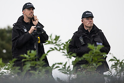 Steeple Claydon, 23rd September, 2020. Thames Valley Police officers watch tree surgeons working with the National Eviction Team on behalf of HS2 Ltd fell a 200-year-old oak tree alongside the East West Rail route known locally as the '7 Sisters Oak' as part of works connected to the HS2 high-speed rail link. A small group of local people and anti-HS2 activists based at the nearby Poors Piece Conservation Project also observed the felling of the tree, which was home to bats and other species, whilst monitored by a joint force of around fifty bailiffs, security guards and police officers from Thames Valley Police.