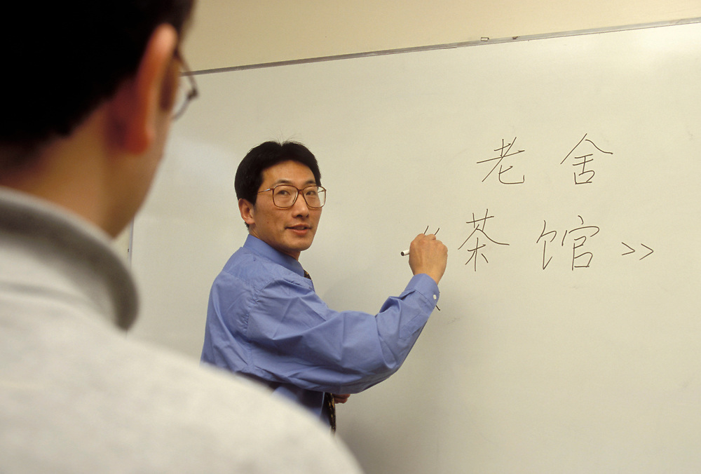 Chinese /Mandarin language class, Tutor writing on whiteboard  in class; University of Westminster; London UK, Text says Lao Tse (famous Chinese author) and Tea House (name of one of his well known books)