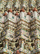 "17 MAY 2013 - BANGKOK, THAILAND:  Hanuman figures support the central prang at Wat Arun. Wat Arun is a Buddhist temple (wat) in the Bangkok Yai district of Bangkok, Thailand, on the west bank of the Chao Phraya River. The full name of the temple is Wat Arunratchawararam Ratchaworamahavihara. The outstanding feature of Wat Arun is its central prang (Khmer-style tower). It may be named ""Temple of the Dawn"" because the first light of morning reflects off the surface of the temple with a pearly iridescence. Steep steps lead to the two terraces. The height is reported by different sources as between 66,80 m and 86 m. The corners are surrounded by 4 smaller satellite prangs. The prangs are decorated by seashells and bits of porcelain which had previously been used as ballast by boats coming to Bangkok from China. The central prang is topped with a seven-pronged trident, referred to by many sources as the ""trident of Shiva"". Around the base of the prangs are various figures of ancient Chinese soldiers and animals. Over the second terrace are four statues of the Hindu god Indra riding on Erawan. The temple was built in the days of Thailand's ancient capital of Ayutthaya and originally known as Wat Makok (The Olive Temple). In the ensuing era when Thonburi was capital, King Taksin changed the name to Wat Chaeng. The later King Rama II. changed the name to Wat Arunratchatharam. He restored the temple and enlarged the central prang. The work was finished by King Rama III. King Rama IV gave the temple the present name Wat Arunratchawararam. As a sign of changing times, Wat Arun officially ordained its first westerner, an American, in 2005. The central prang symbolizes Mount Meru of the Indian cosmology. The satellite prangs are devoted to the wind god Phra Phai.     PHOTO BY JACK KURTZ"