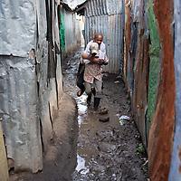 A man carries another man on his back over puddles in MJukuru Kwa Njenga, Nairobi