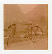 """Polaroid chocolate picture of a bicycle along the road. It looks like bicycle style in 1940""""s. Guangxi province, China, Asia."""