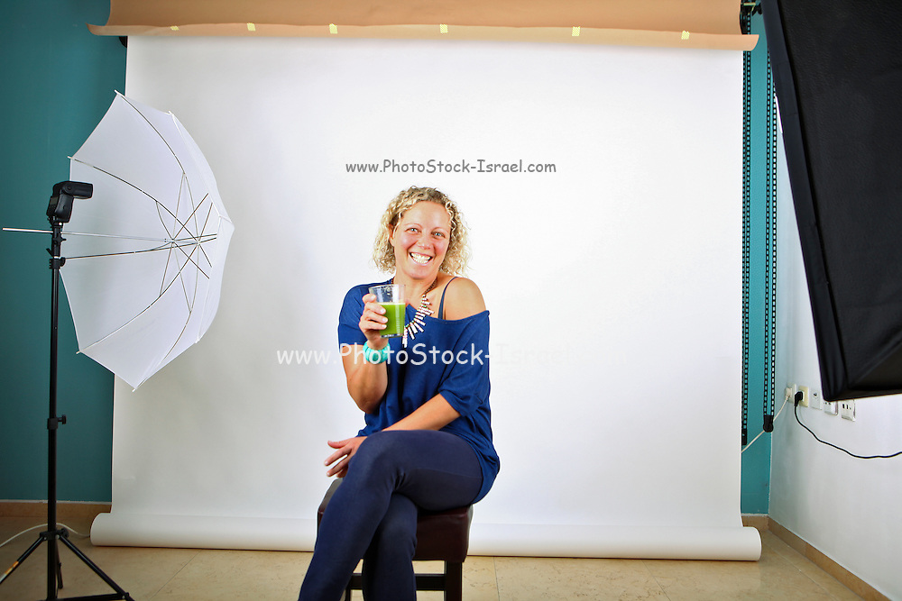Model in photography studio drinking wheatgrass on the set