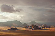 Sunlight filters through dark clouds onto sandstone cliffs of Wadi Rum, Jordan.