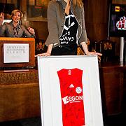 NLD/Amsterdam/20100328 - Veiling voor Engelen van Oranje, Fanny Koopmans, partner van Boy Waterman toont gesigneerd shirt van Ajax spelers