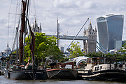 With Tower Bridge and the Walkie Talkie building in the distance, barges and lighters at Tower Bridge Moorings are grouped together on the river Thames, on 11th June 2021, in London, England. Xylonite is one of seven Thames barges built between 1925 and 1930. Tower Bridge Moorings is the capital's only floating gardens - a sustainable way of living for a community of more than one hundred adults and children, and a shelter for wildlife on the river.