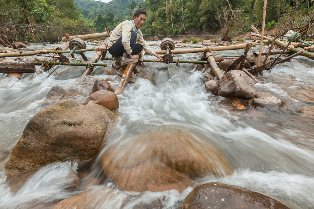 A man adjusts the (boat) propeller on a micro hydro turbine in the flow of the Nam Ou River at Ban Sop Kha, Laos. The turbines are used by villages all along the river to generate electricity, at least during the dry season when the water level is low enough to mount them to the river bed.