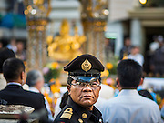 21 AUGUST 2015 - BANGKOK, THAILAND: A Thai police officer at the Erawan Shrine Friday. The Bangkok Metropolitan Administration (BMA) held a religious ceremony Friday for the Ratchaprasong bomb victims. The ceremony started with a Brahmin blessing at Erawan Shrine, which was the target of a bombing Monday night. After the blessing people went across the street to the plaza in front of Central World mall for an interfaith religious service. Theravada Buddhists, Mahayana Buddhists, Muslims, Sikhs, Hindus, and Christians participated in the service. Life at the shrine, one of the busiest in Bangkok, is returning to normal. Friday the dancers and musicians who perform at the shrine resumed their schedules.     PHOTO BY JACK KURTZ