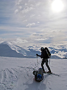 Alaska, Denali National Park.  A ski mountaineer descendes Denali with a sled full of equipment in tow.