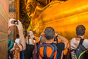 26 NOVEMBER 2012 - BANGKOK, THAILAND:  Tourists walk through hall housing the Reclining Buddha in Wat Pho, also called the Temple of the Reclining Buddha in Bangkok. Thailand's Temple of the Reclining Buddha has gained further global prominence following a 45-minute tour by U.S. President Barack Obama and Secretary of State Hillary Clinton during their November 18-19 visit to the kingdom. Known also as the Temple of the Reclining Buddha, its official name is Wat Phra Chettuphon Wimon Mangkhlaram Ratchaworamahawihan. The temple is also known as the birthplace of traditional Thai massage. There is a popular massage school on the temple grounds.    PHOTO BY JACK KURTZ