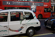 A man in a hammock advertises an investment and pensions savings company on a taxi cab with an ad for the latest James Bond film Spectre, on DVD soon. The traffic is heavy on Oxford Street with standstill cars and buses along this shopping road running east/west through central London. Cabs are back-to-back as they await the next fares and red buses host advertising for films and musicals such as this one for Spectre (2015).