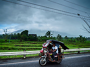 20 JANUARY 2018 - CAMALIG, ALBAY, PHILIPPINES: A Filipino tuk-tuk passes Mayon volcano, which is blanketed in clouds. More than 30,000 people have been evacuated from communities on the near the Mayon volcano in Albay province in the Philippines. Most of the evacuees are staying at school in communities outside of the evacuation zone.   PHOTO BY JACK KURTZ