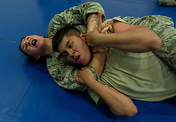 Airman 1st Class Victoria Goehner, 18th Security Forces Squadron  response force member, places Airman 1st Class Ronald Martinez, 18th SFS response force member, in a choke hold during combatives training June 12, 2018, at Kadena Air Base, Japan. (U.S. Air Force photo by Staff Sgt. Micaiah Anthony)